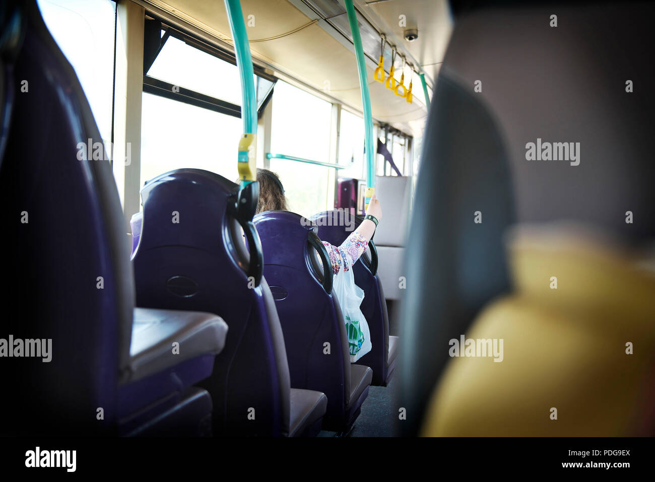 young white female sits on an empty bus during the commute to work, with a view from the back seats - Stock Image