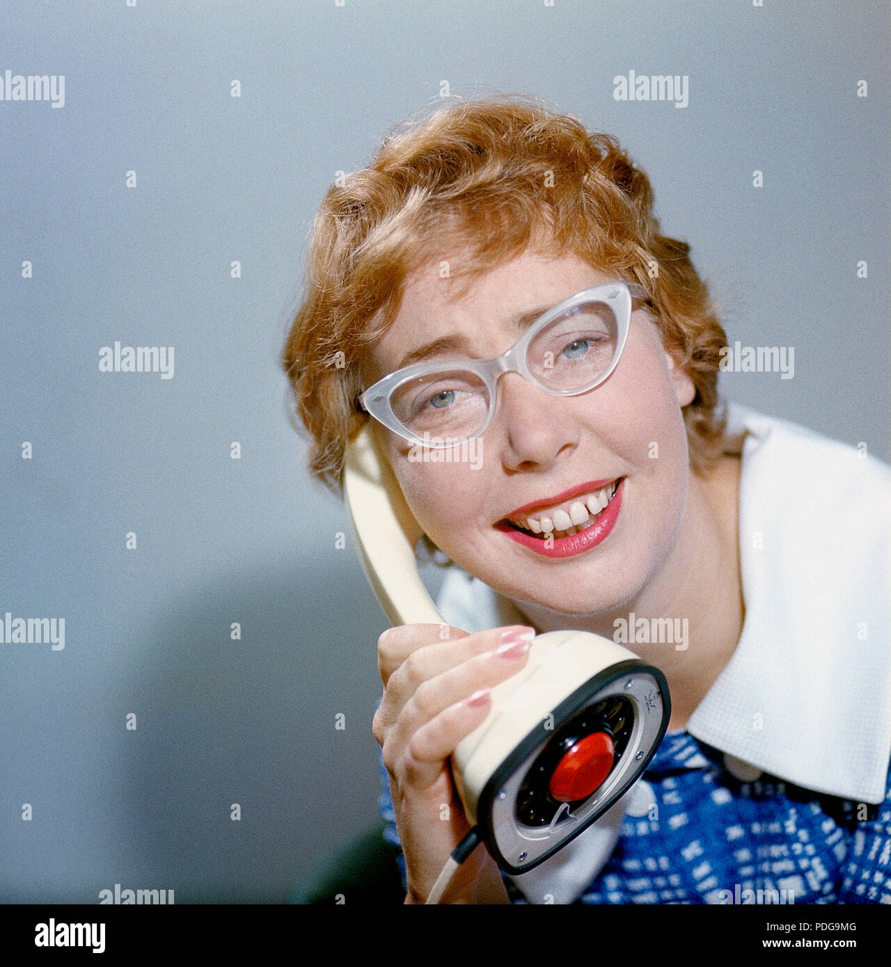 1950s glasses and telephone. A young woman in typical fifties glasses and bows is talking on the telephone.  Swedish on-piece plastic telephone created by Ericsson Company of Sweden and launched 1956. Because of its styling and its influence on future telephone design, the Ericofon is considered one of the most significant industrial designs of the 20th century. The idea was to incorporate the dial and handset into one single unit. To call, you lifted it up and dialed the number, and to end the call, you put the phone down.  The model is also known as the Cobra telephone for its resemblance to - Stock Image