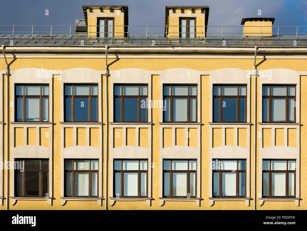 The facade of the old building with yellow walls and white décor on ...