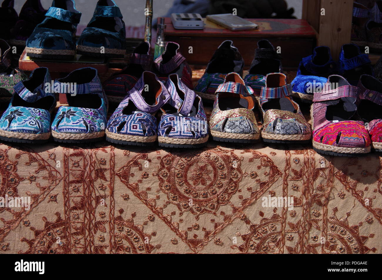 Colourful Fabric Women's Shoes at a Market Stand. Sidmouth Folk Festival, East Devon, UK. August, 2018. - Stock Image