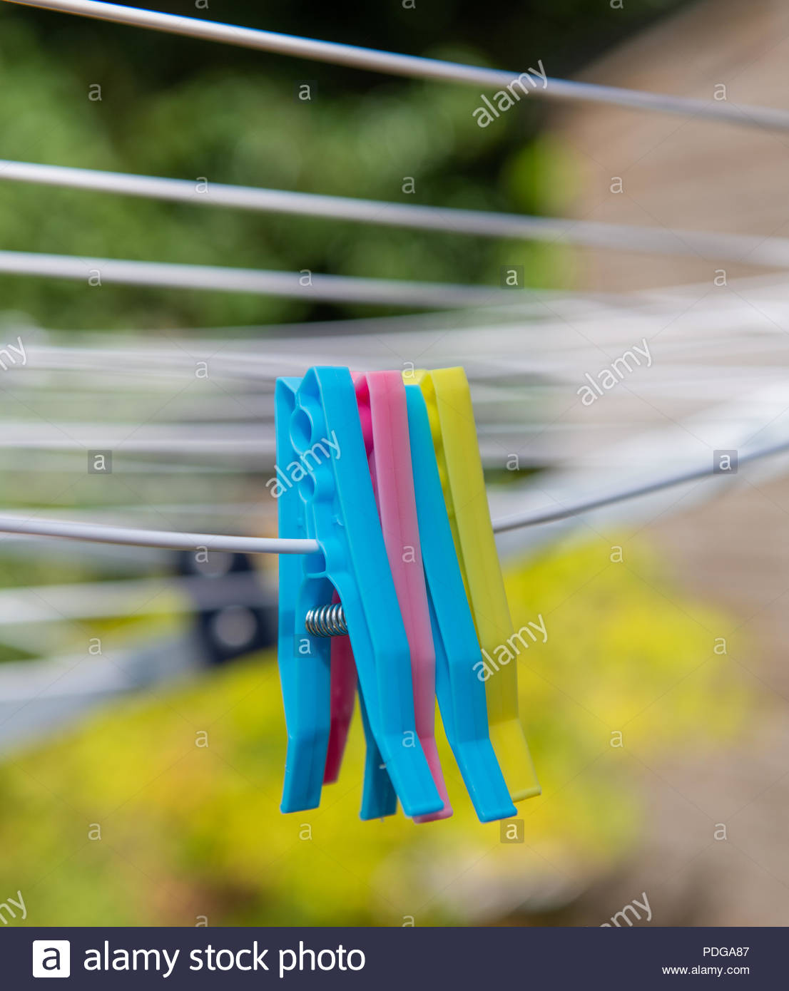 Four colourful plastic pegs hanging on a washing line. - Stock Image