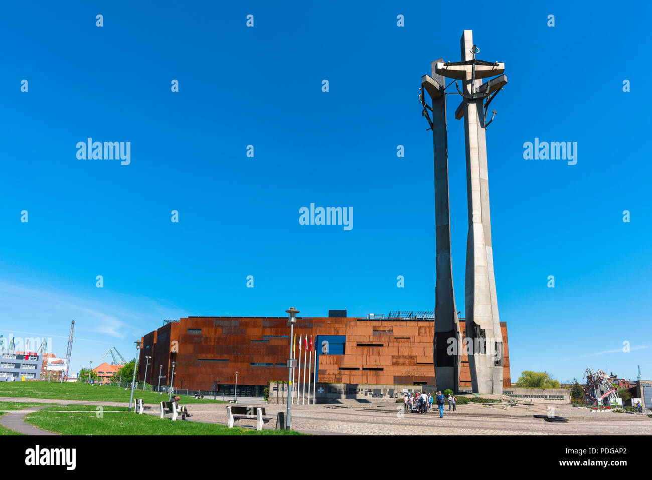 View of the 42 metre tall Monument To The Fallen Shipyard Workers in Gdansk, with the European Solidarity Centre Museum building at rear, Poland. Stock Photo
