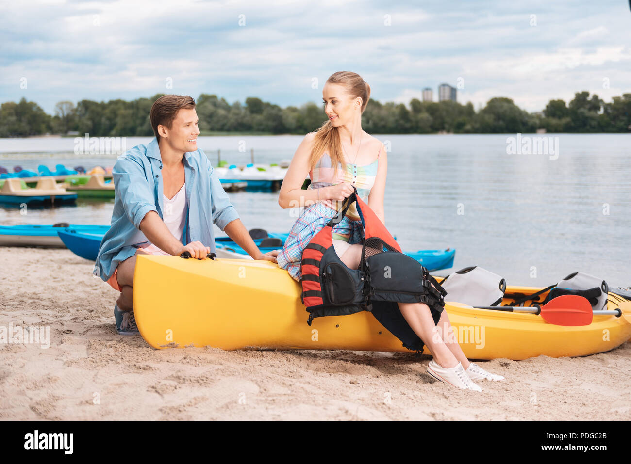 Blonde-haired girlfriend holding life vest while preparing for kayaking - Stock Image