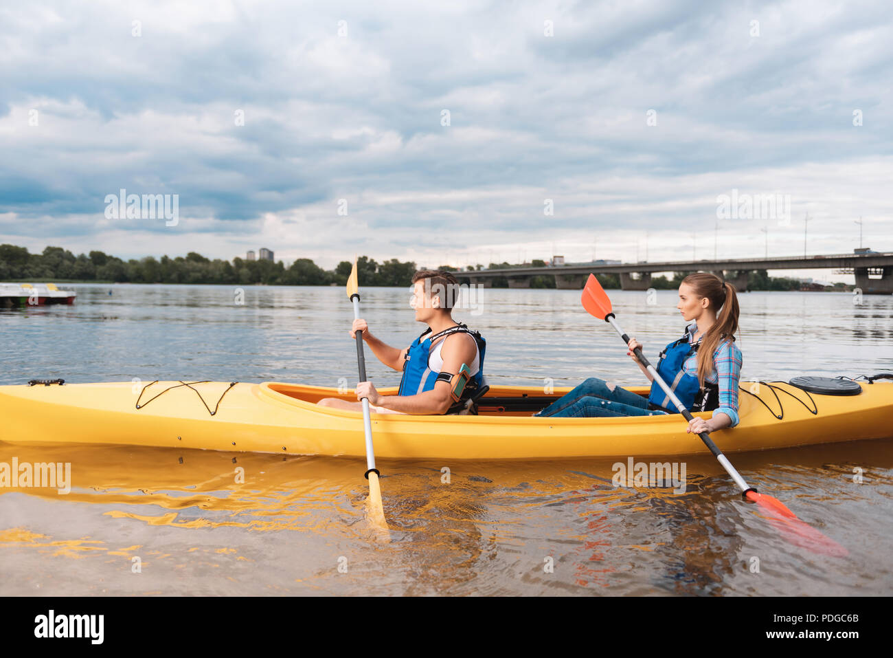 Modern couple holding paddles while kayaking on weekend - Stock Image