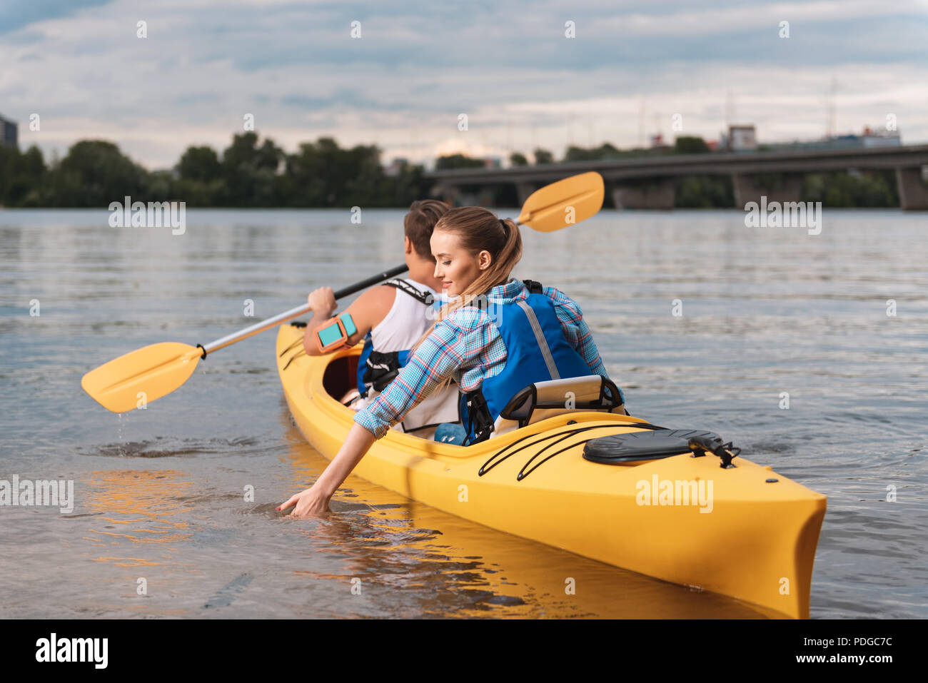 Athletic woman wearing life vest sitting in yellow canoe with trainer - Stock Image