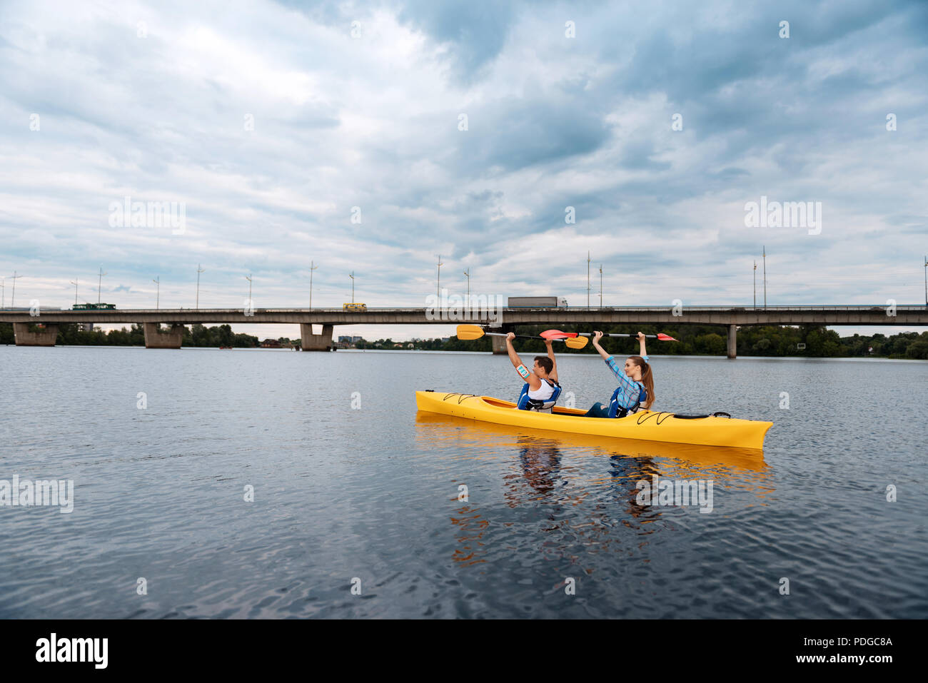 Active sportsmen rowing in canoe lifting their paddles - Stock Image