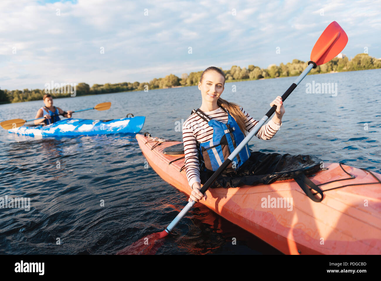 Good-looking woman wearing striped shirt and life vest kayaking - Stock Image