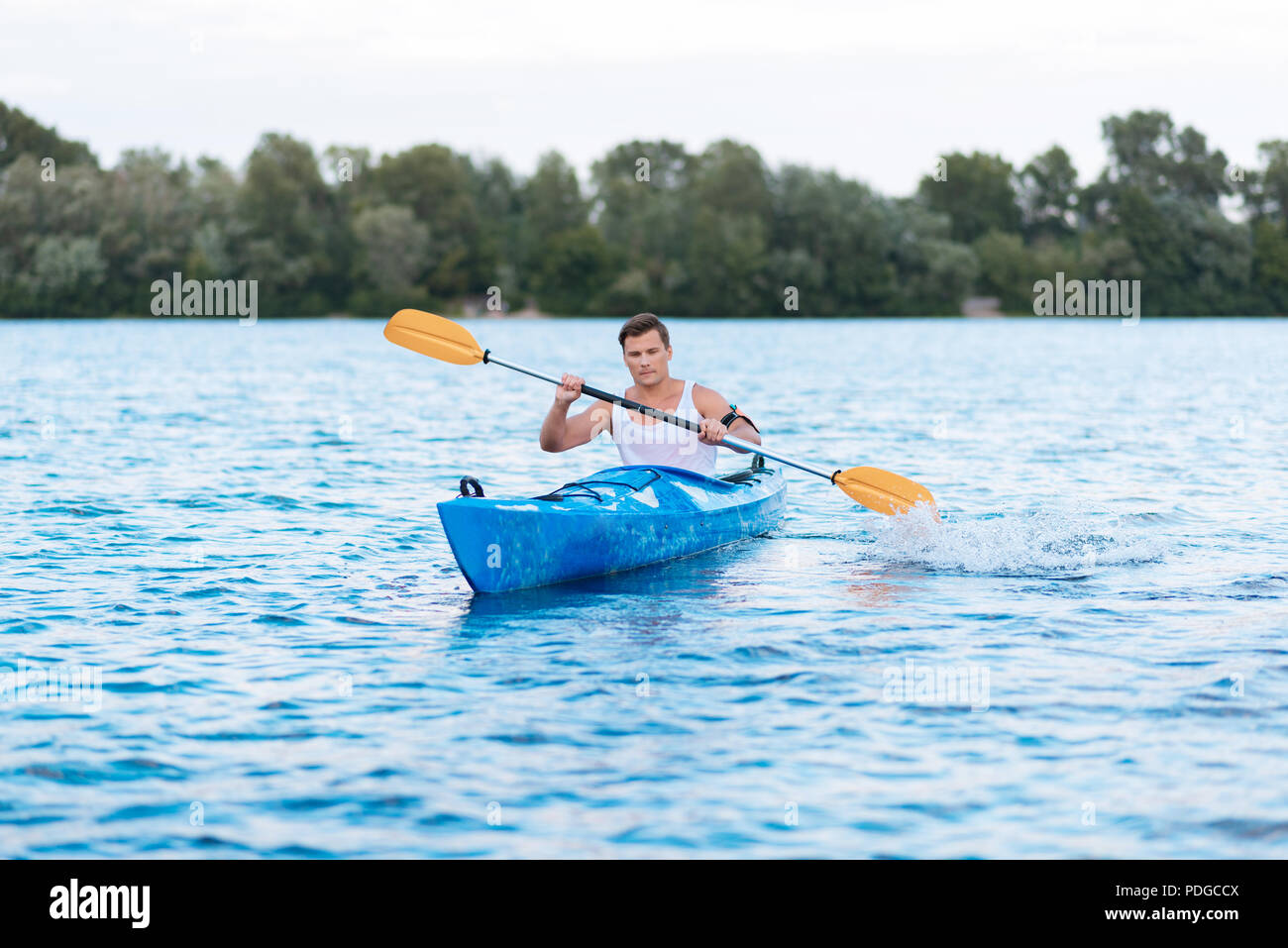 Strong muscle man holding paddles while rowing in canoe - Stock Image