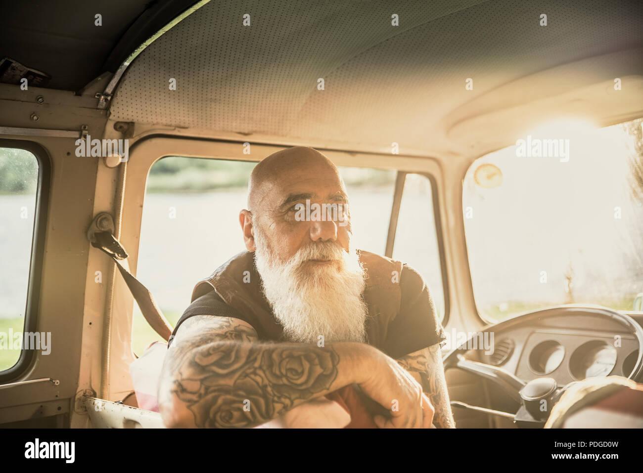 Portrait of a senior hipster inside their vintage van  - Stock Image