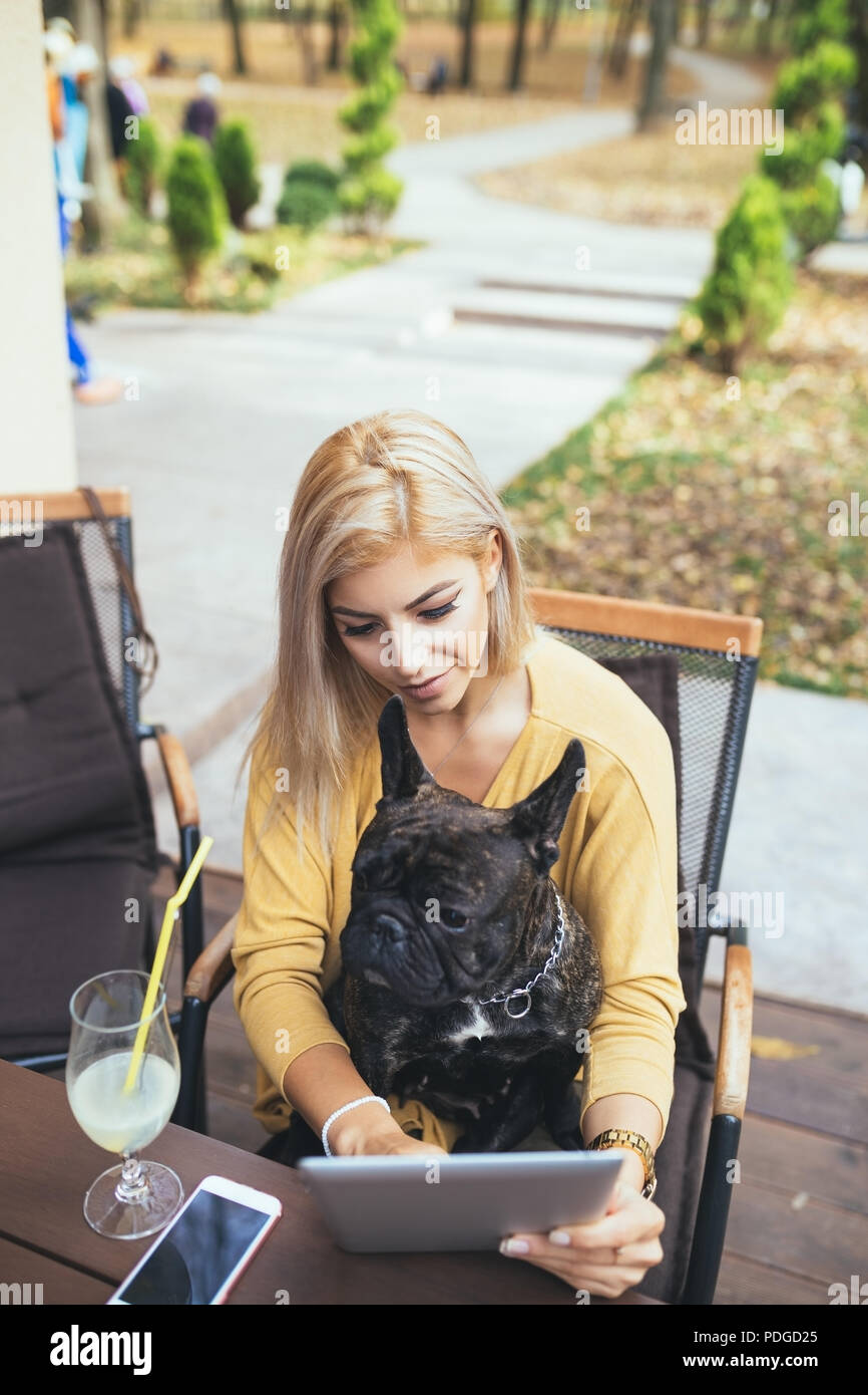 Beautiful and happy blonde woman with tablet enjoying in cafe bar with her adorable French bulldog. - Stock Image