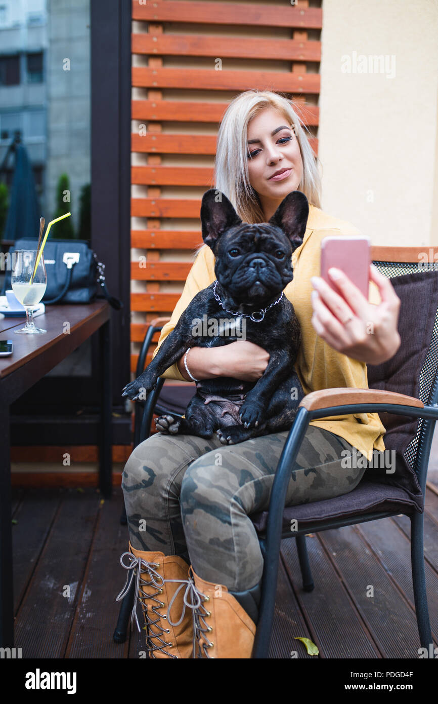 Beautiful and happy blonde woman enjoying in cafe bar and taking selfie photo with her adorable French bulldog. - Stock Image