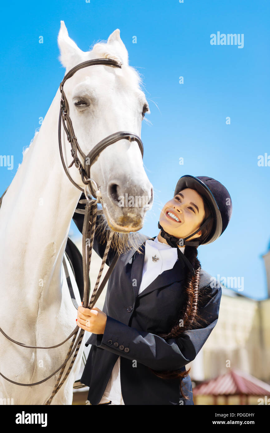 Dark-haired rider with long braid preparing for horse riding - Stock Image