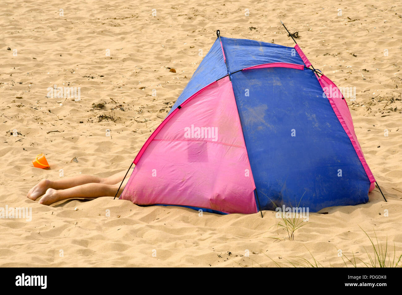 Person lying on a sandy beach partly in a tent with legs sticking out - Stock Image
