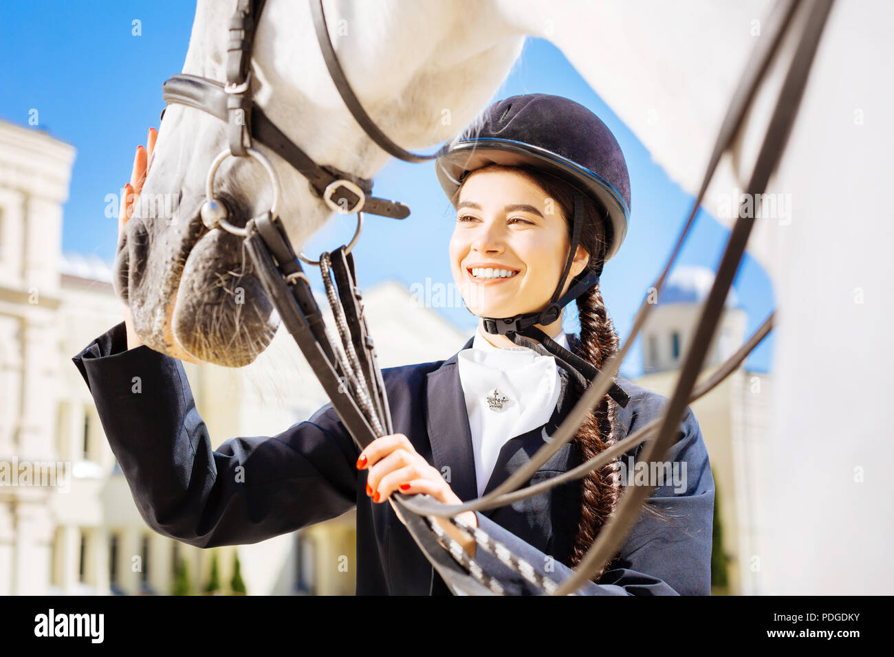 Beaming dark-haired horsewoman petting her white horse - Stock Image