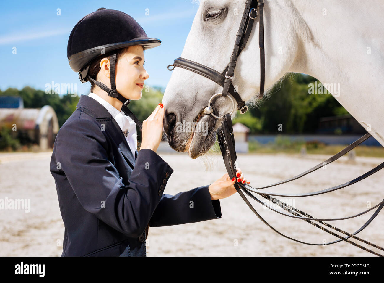 Appealing horsewoman looking into eyes of her white horse - Stock Image