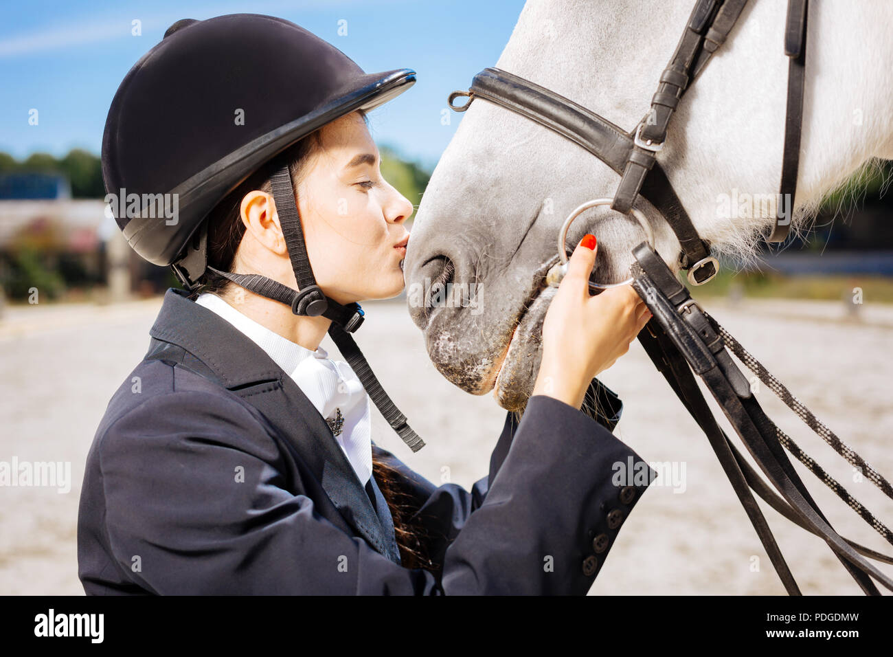 Loving horsewoman with red nail art kissing her white horse - Stock Image