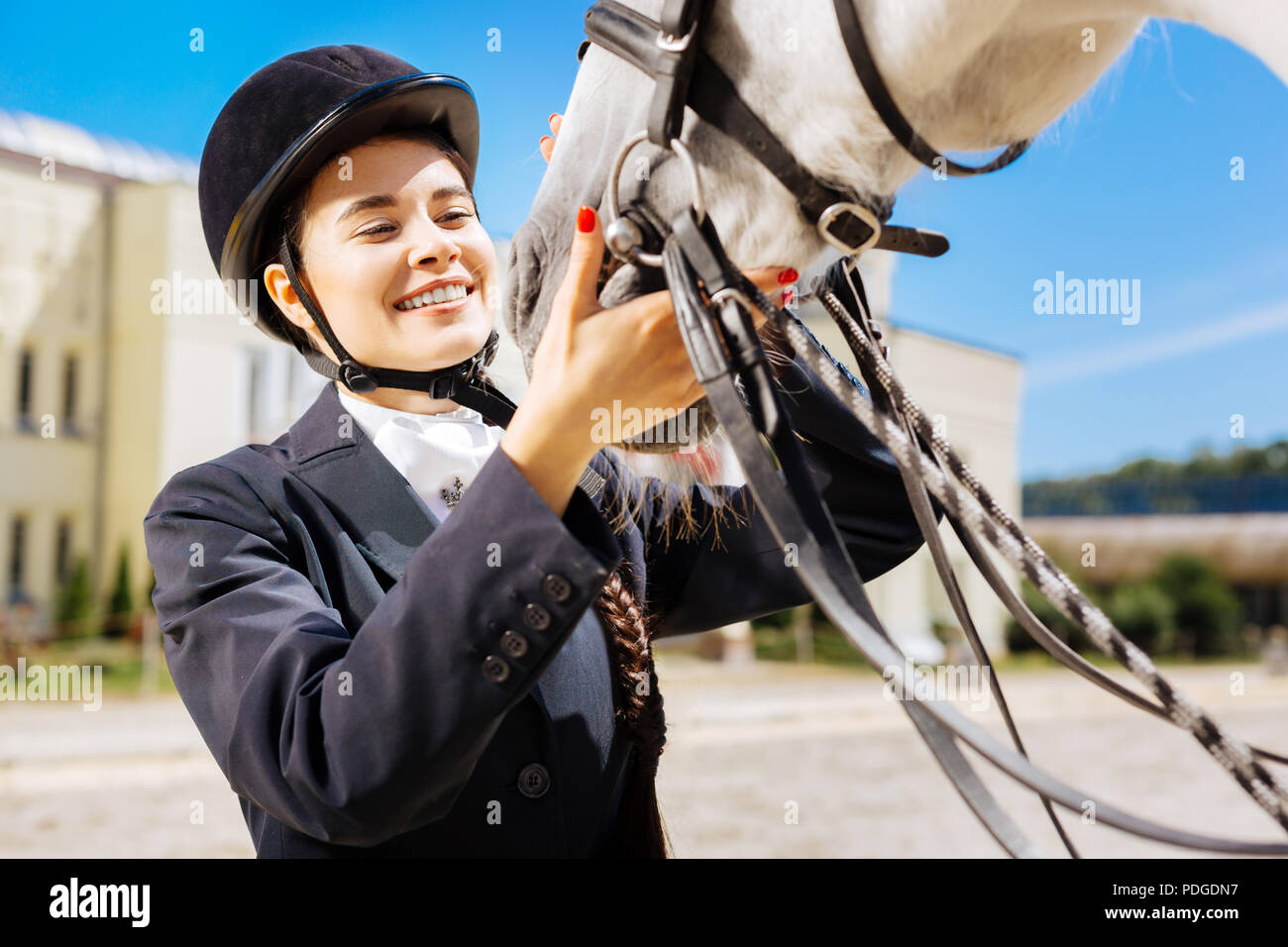 Woman wearing dark jacket taking care of white racing horse - Stock Image