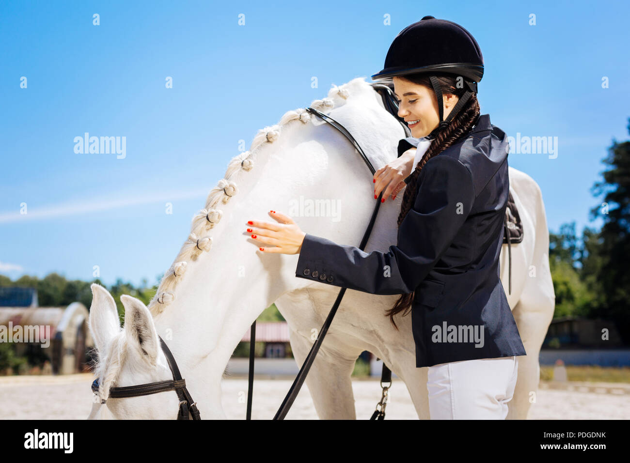 Appealing female rider wearing white trousers and dark jacket - Stock Image