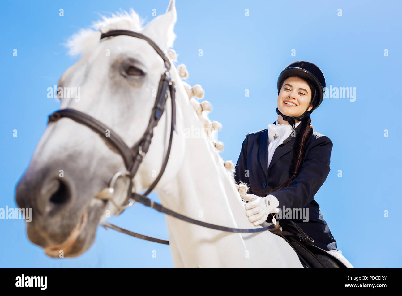 Horsewoman wearing white gloves sitting on her white horse - Stock Image