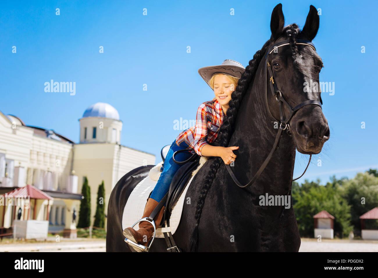 Cute cowboy girl hugging her beautiful black horse - Stock Image