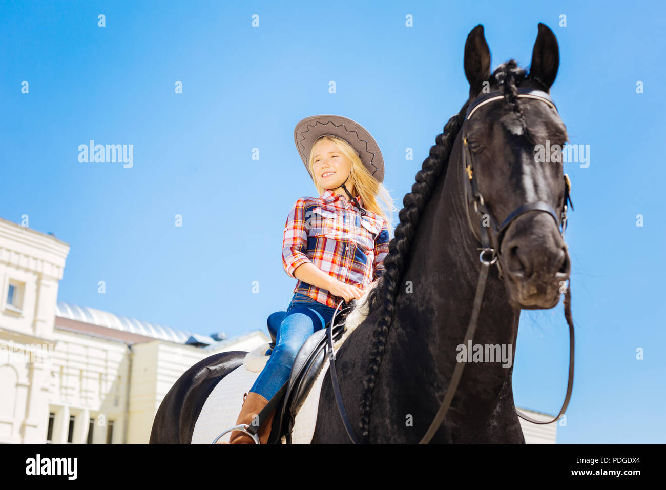Smiling girl wearing jeans and riding boots sitting on dark horse - Stock Image