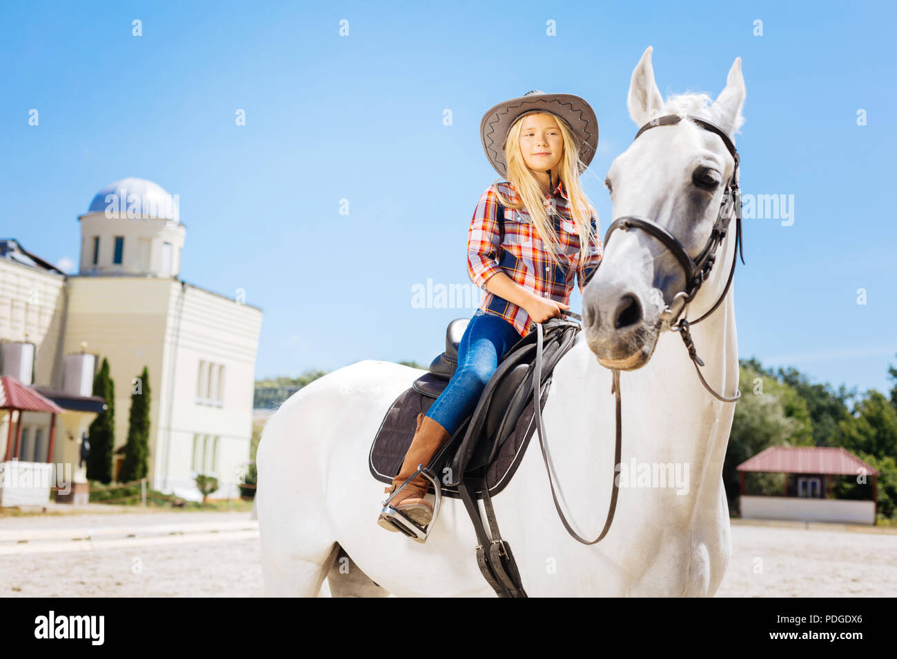 Blonde-haired cowboy girl wearing stylish clothes riding horse - Stock Image