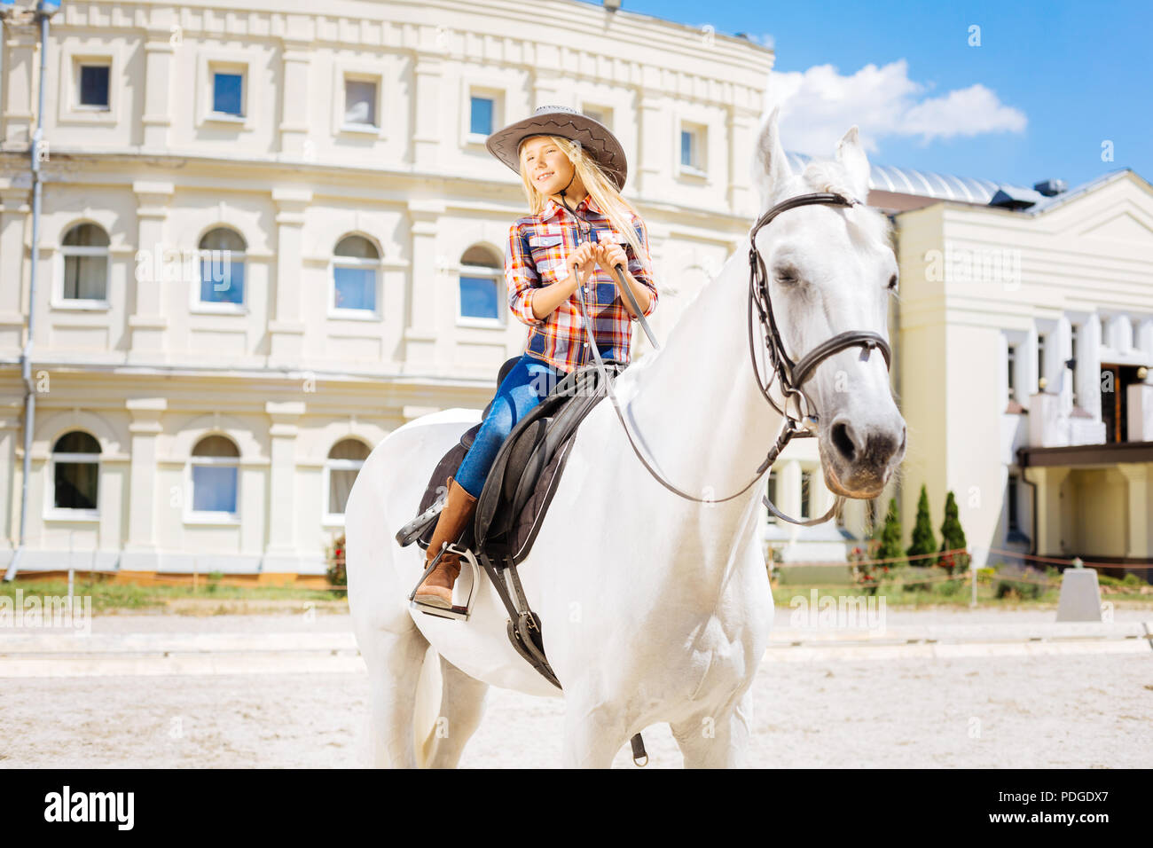 Cute schoolgirl fond of equestrianism riding horse on weekend - Stock Image