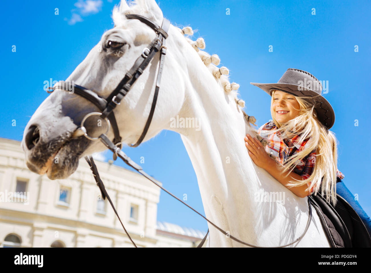 Smiling cute cowboy girl leaning on her white racing horse - Stock Image