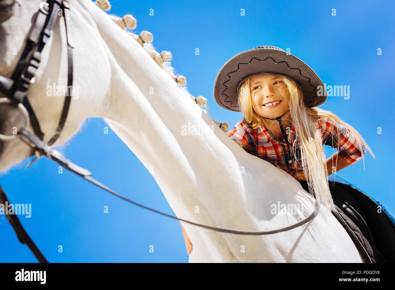 Cute smiling girl petting white racing horse while sitting on him - Stock Image