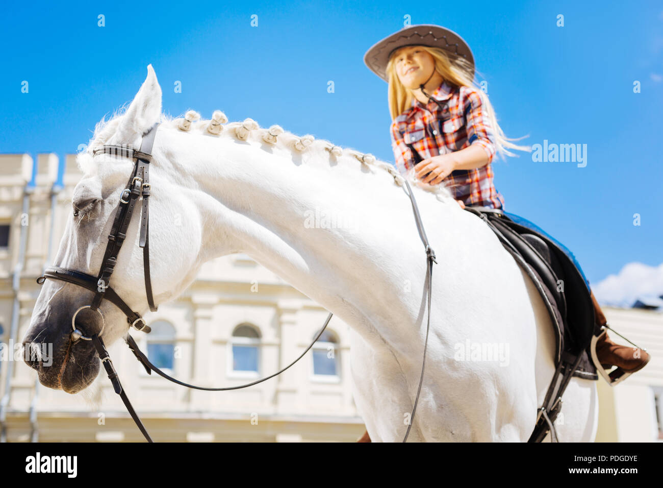 Stylish cowboy girl wearing brown riding boots riding horse - Stock Image