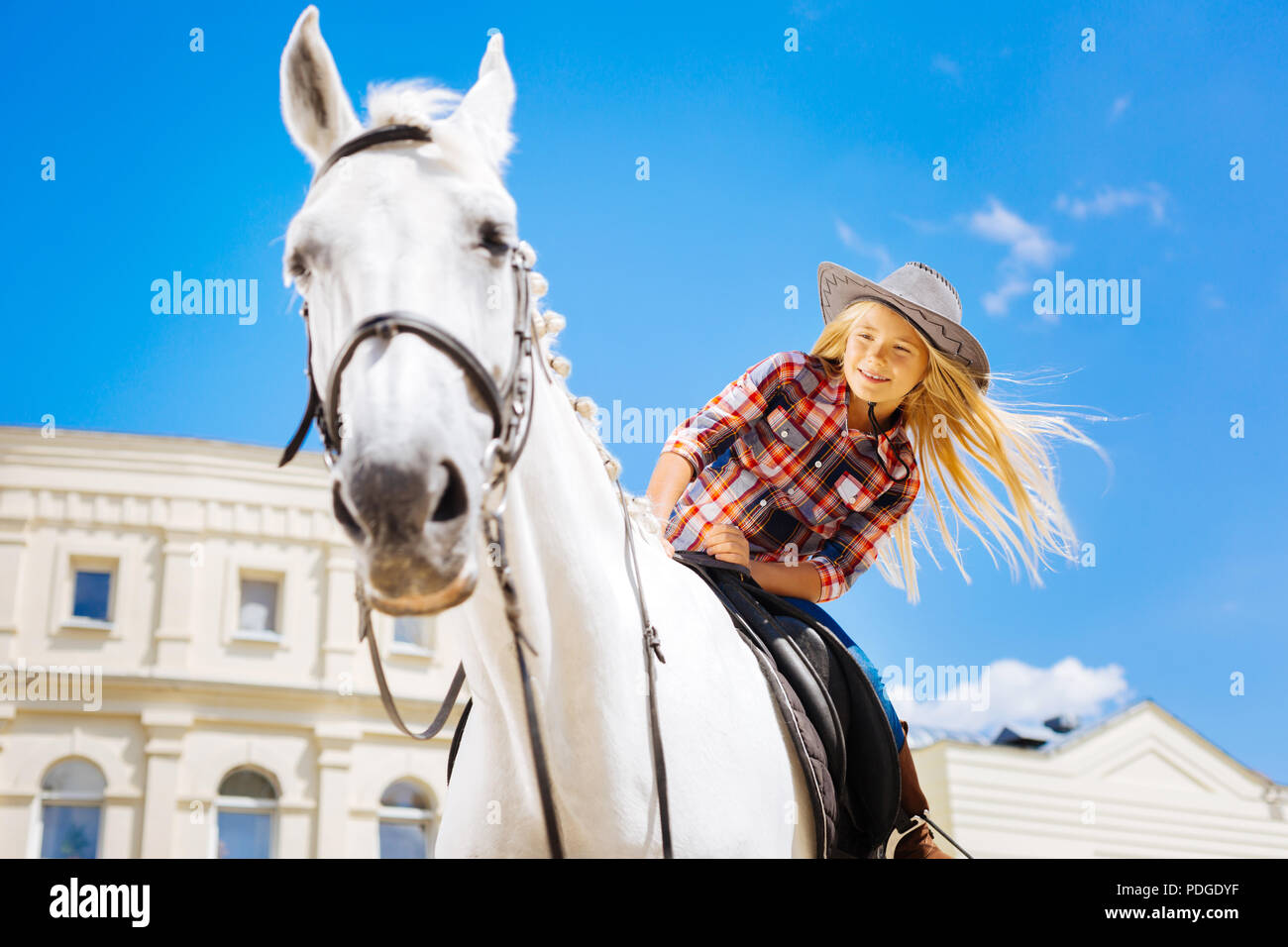 Beaming schoolgirl enjoying her horse riding lesson - Stock Image