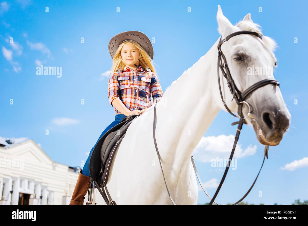 Stylish schoolgirl sitting on white gentle racing horse - Stock Image