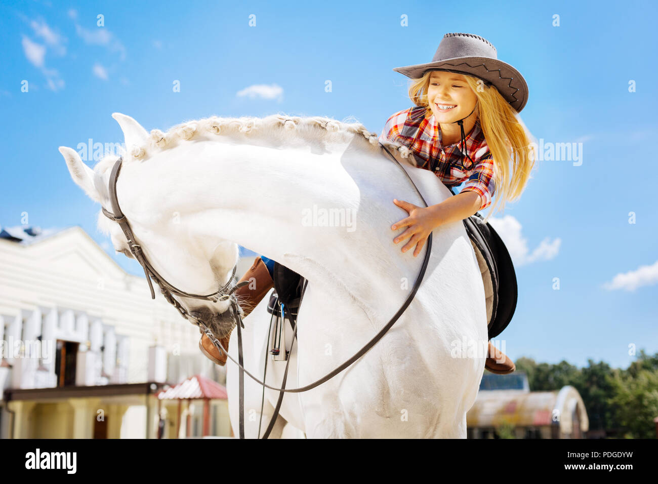 Beautiful cowboy girl having fun while riding her lovely horse - Stock Image