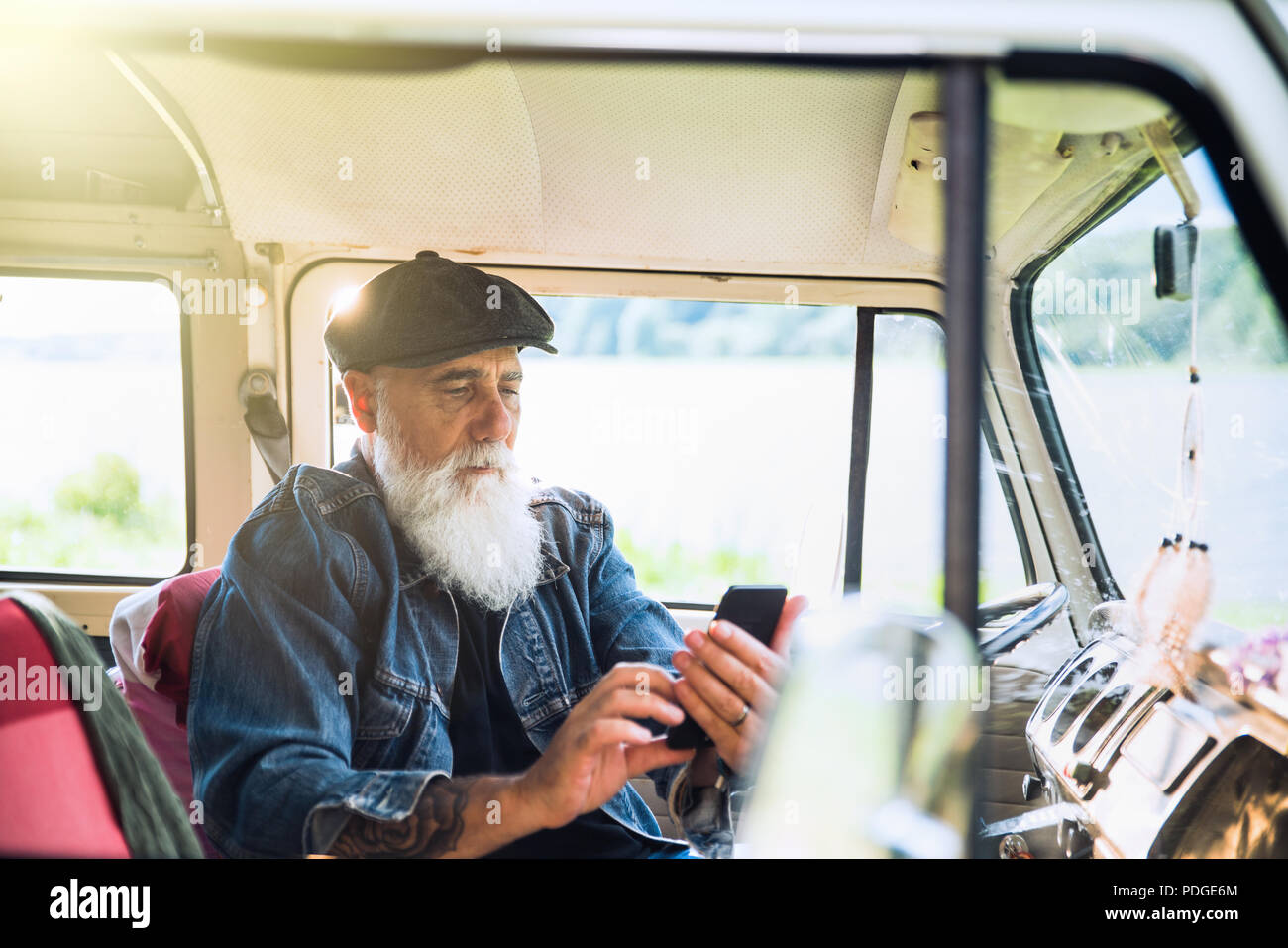 A senior hipster sitting in his camper van, using a phone. - Stock Image