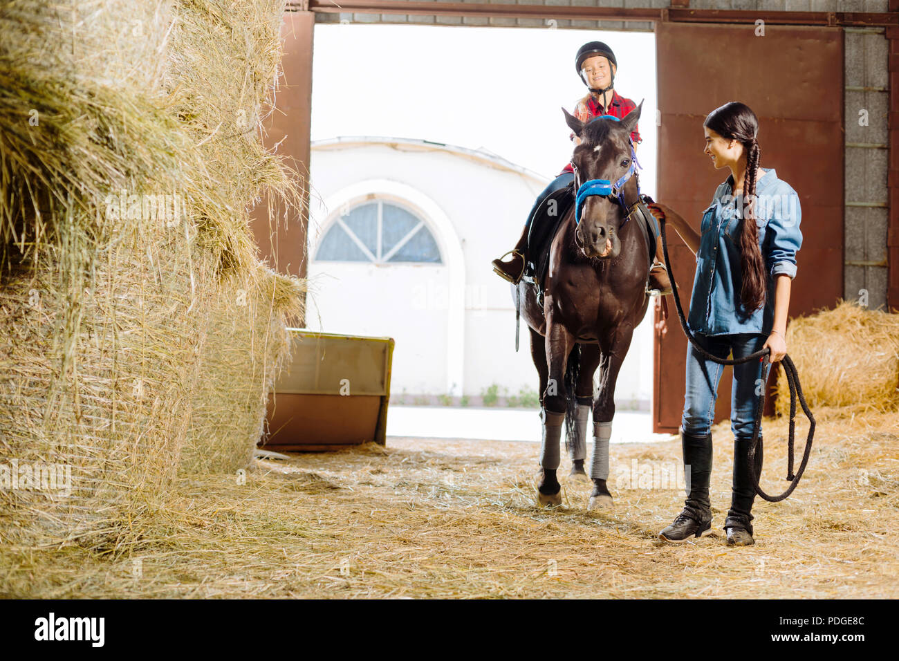 Horsewoman teaching her daughter riding racing horse - Stock Image