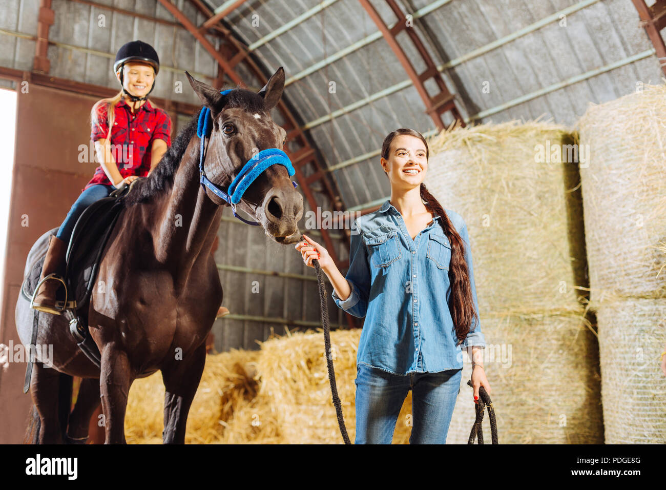 Dark-haired stylish riding teacher leading horse with cute girl - Stock Image