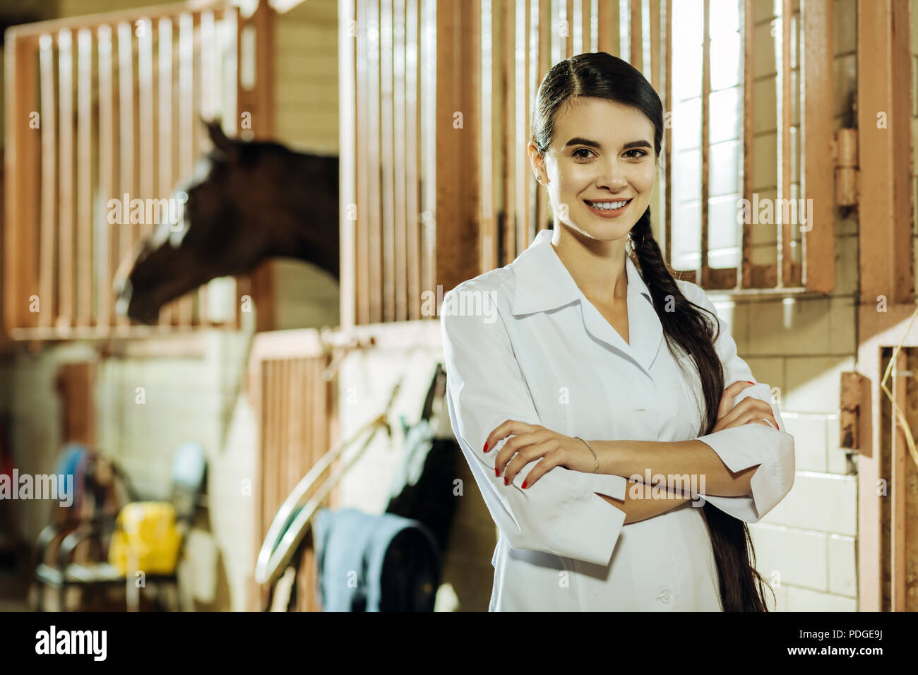 Dark-eyed woman wearing white uniform standing in stable - Stock Image