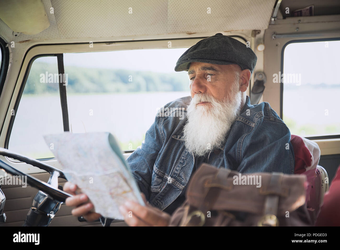 A senior man seated in his camper van looks at a road map - Stock Image