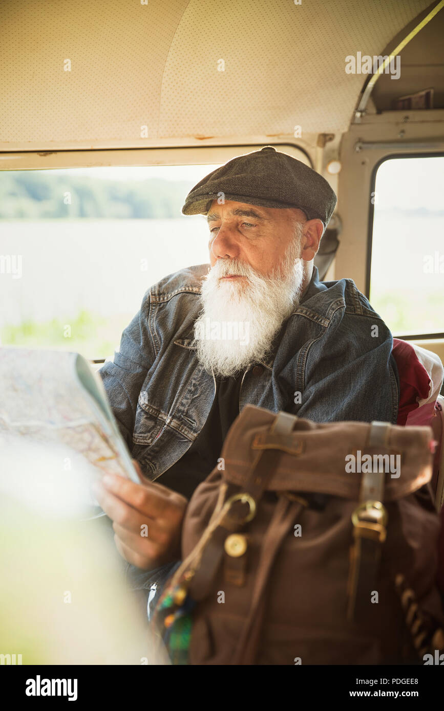 A senior man seated in his vintage van looks at a road map - Stock Image