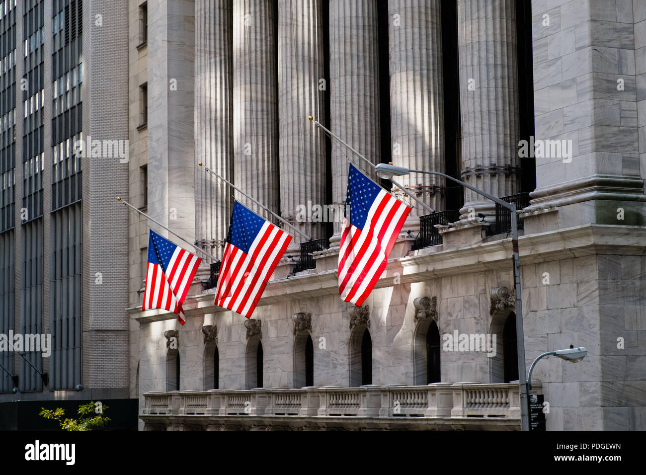 Backlit flags in front of the portico of New York Stock Exchange, Wall Street, Manhattan, New York City - Stock Image