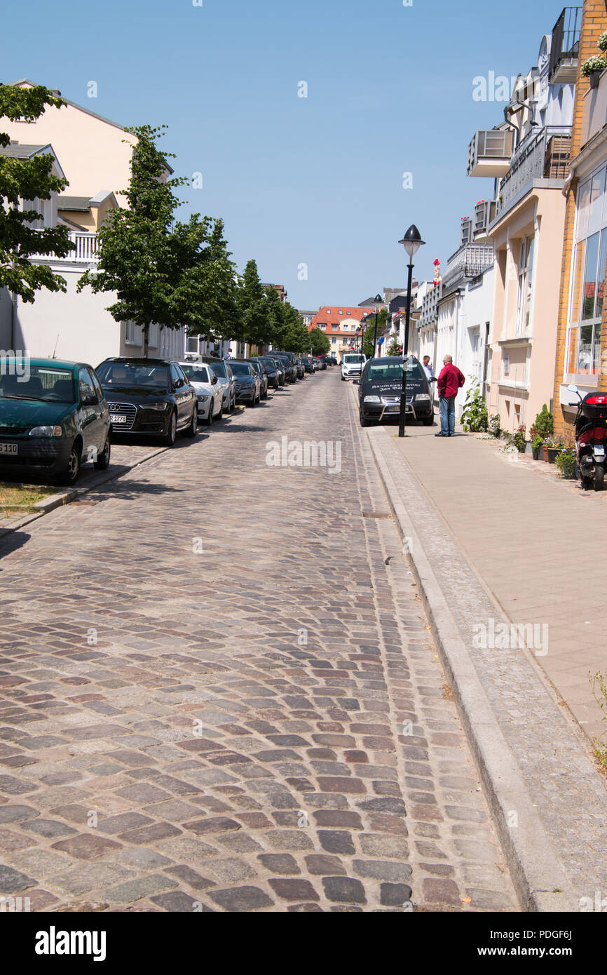 Narrow european cobblestone street with brick sidewalks lined with houses and cars parked on the sidewalk because the street is too small to keep the  - Stock Image