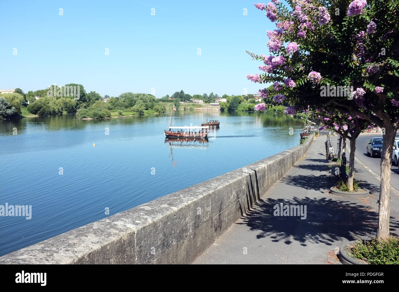 A river boat crosses the River Dordogne  in the city of Bergerac, south west France in the hot August of 2018. - Stock Image