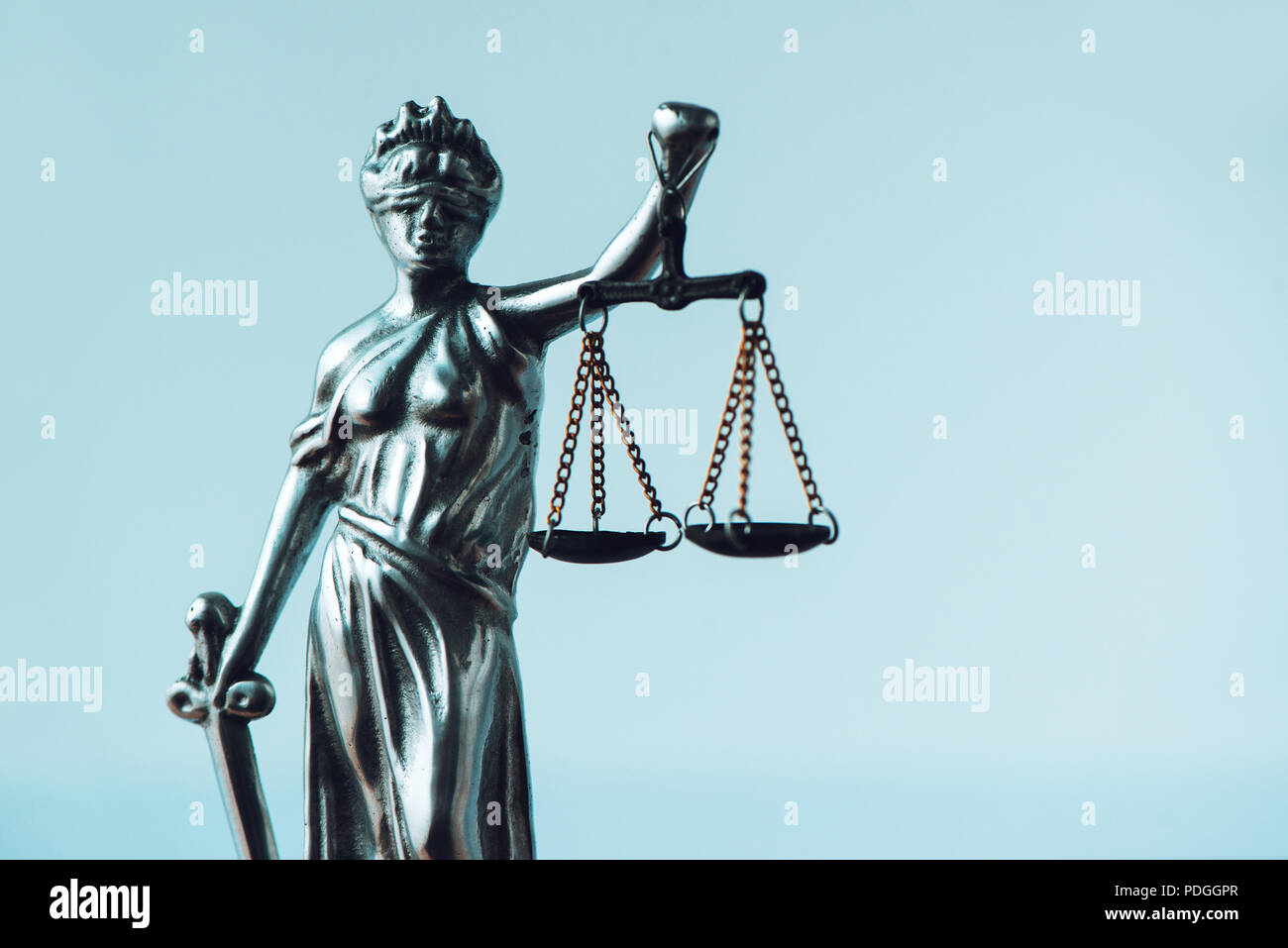 Lady Justice statue in law office. Figurine with blindfold, balance and sword is personification of moral force in judicial system and it's origin is  - Stock Image