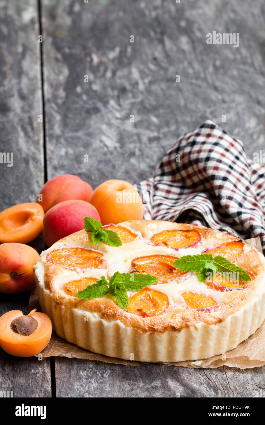 Homemade  cheese cake with apricot on wooden table - Stock Image