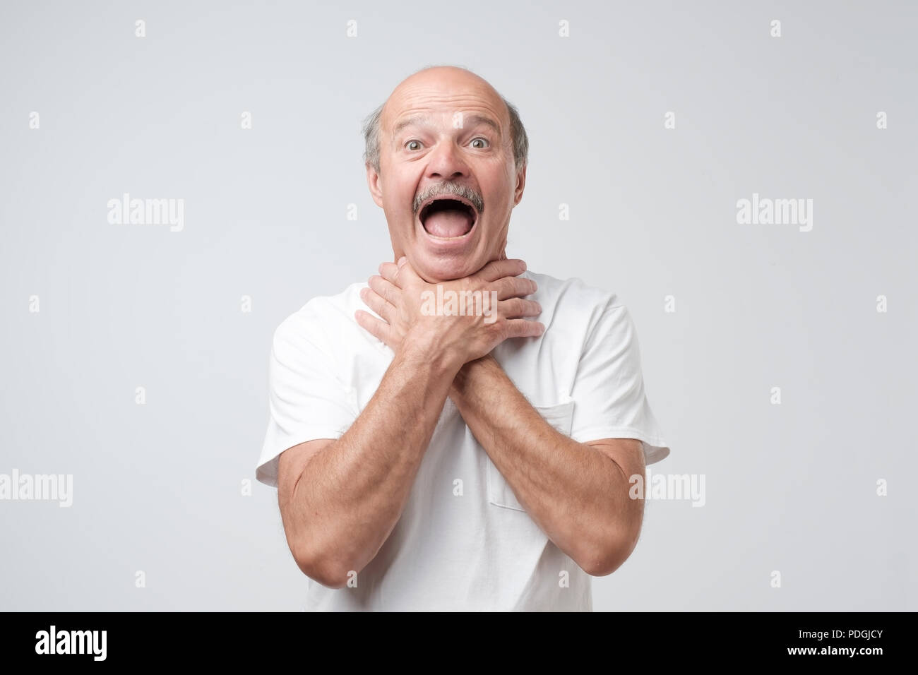 Mature european man in white tshirt shouting and suffocate because painful strangle. Health problem. Asphyxiate and breathing problem concept. - Stock Image