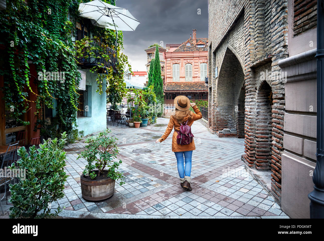 Tourist woman in brown hat walking down old the Old streets of central Tbilisi, Georgia - Stock Image