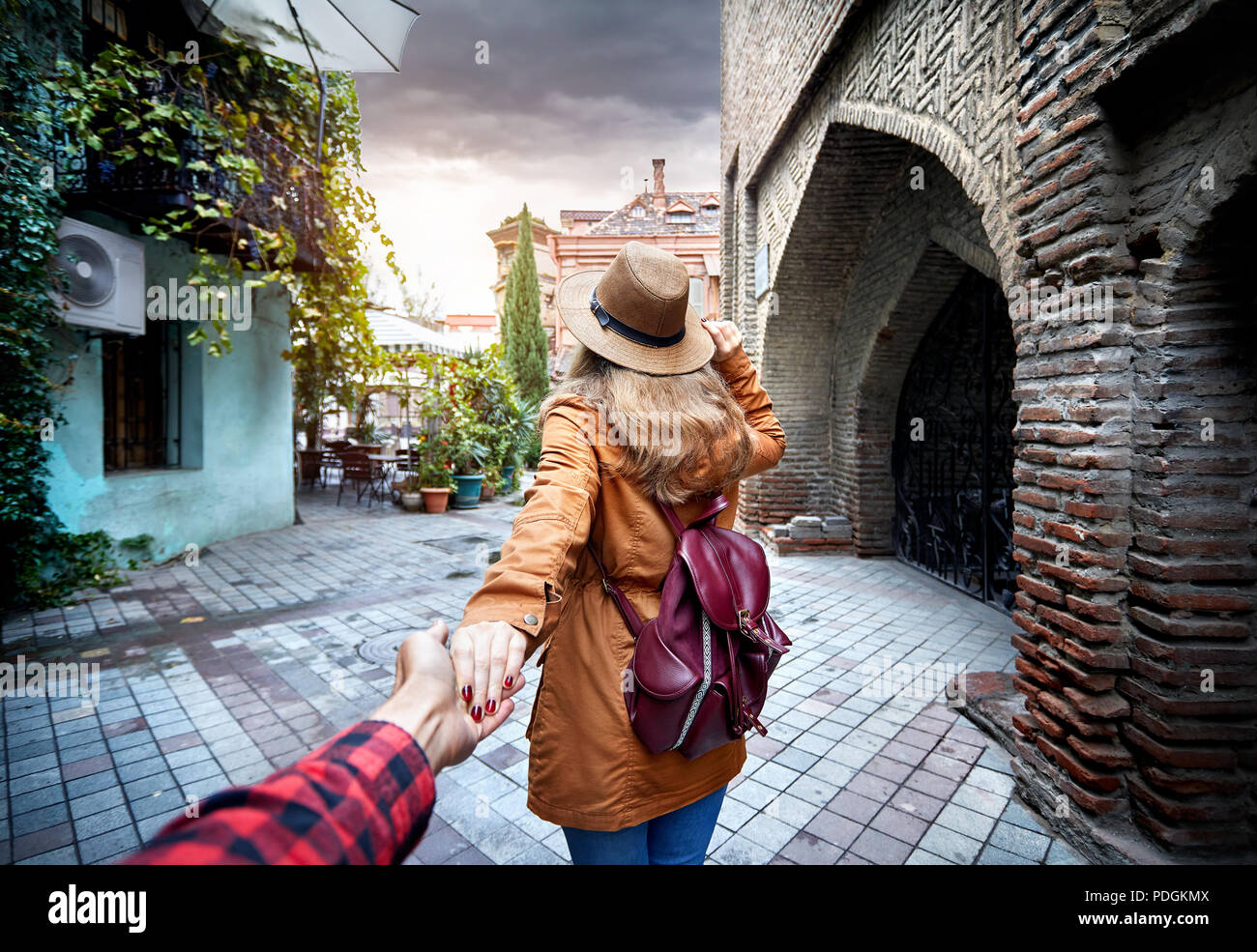 Woman in hat and brown jacket leading man to the narrow street in old, Georgia - Stock Image