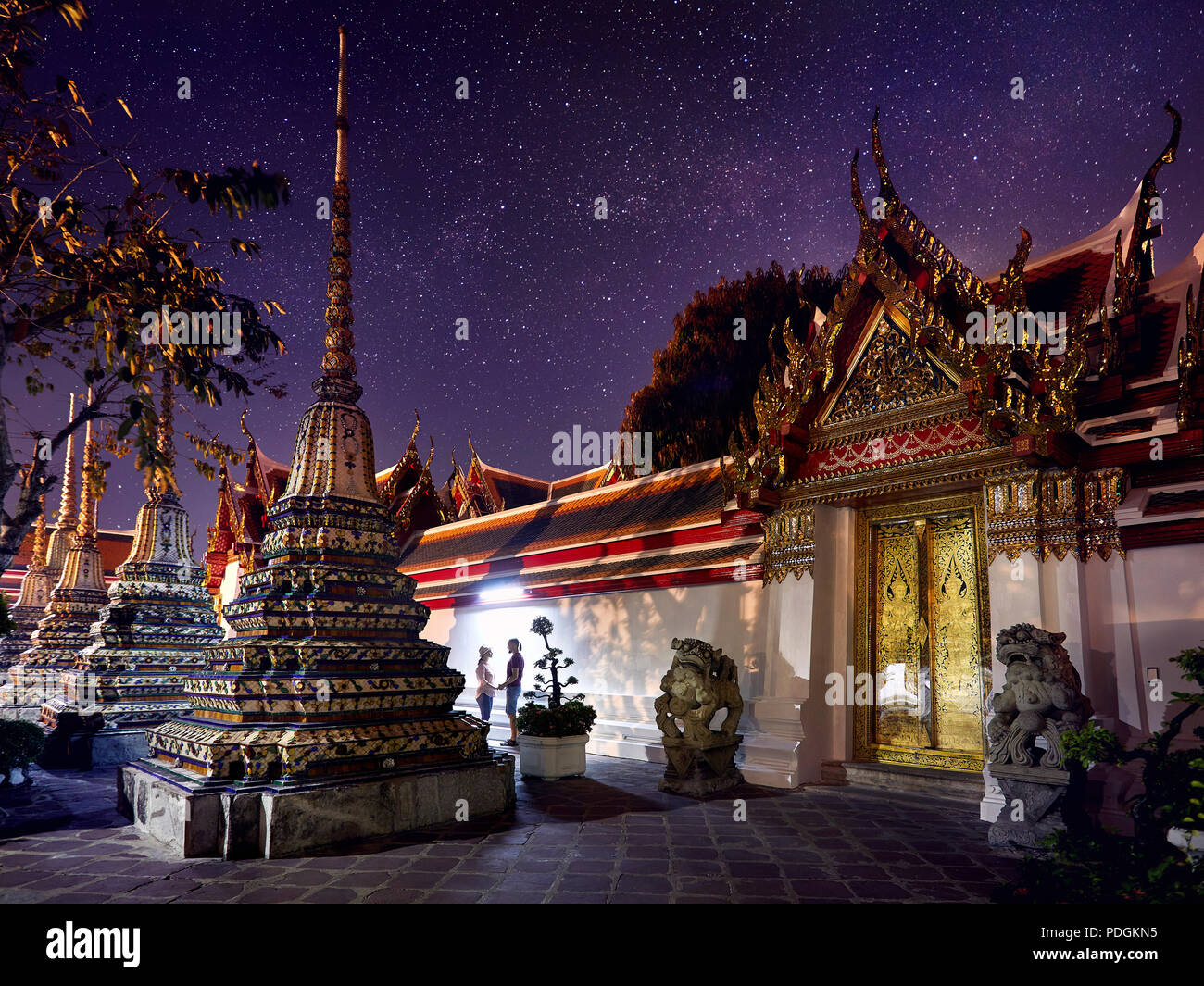 Young Couple in Buddhist temple complex Wat Pho in Bangkok at magical night starry sky at background in Thailand - Stock Image