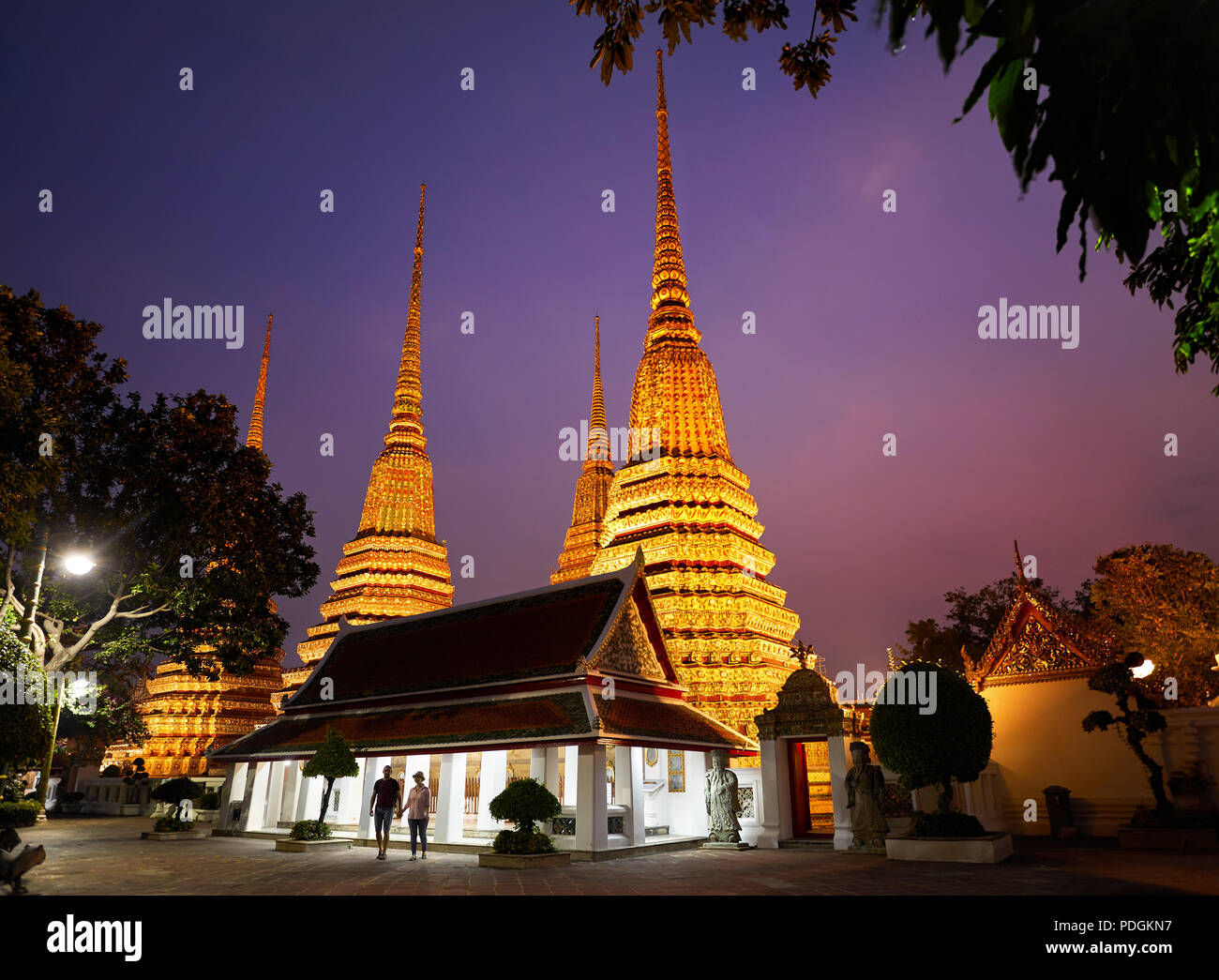 Young Couple in silhouette at Buddhist temple complex Wat Pho in Bangkok purple night sky in Thailand - Stock Image