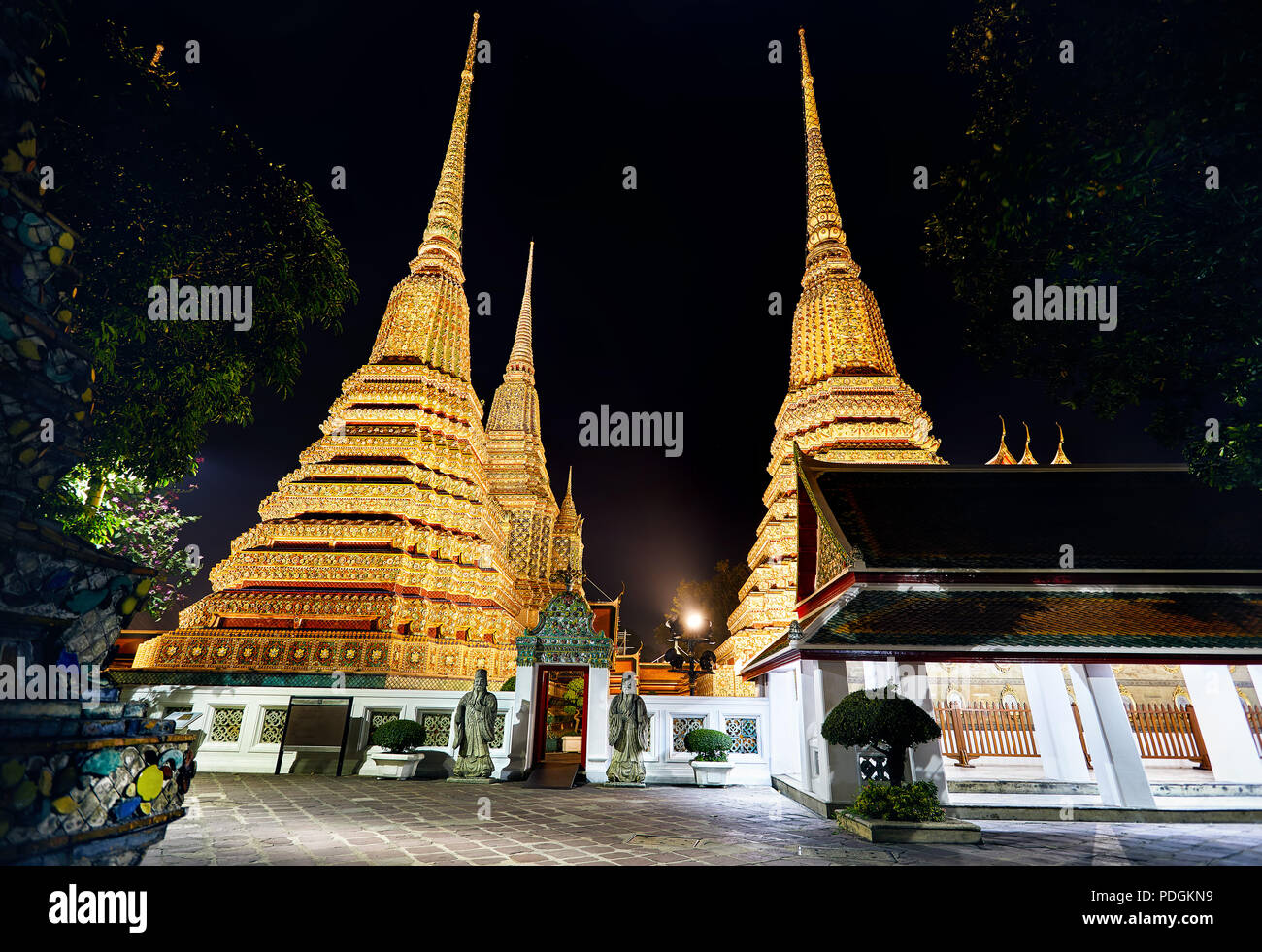 Buddhist Temple Wat Pho with golden Chedi in Bangkok at night sky in Thailand. Famous landmark and sight of the city. Stock Photo